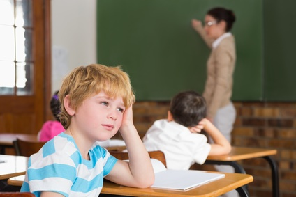 Cute pupil not paying attention in classroom