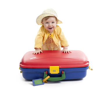 laughing baby with red and blue suitcase, on white